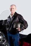 Studioporträt eines älteren Mannes, der sein Motorrad lokalisiert auf Weiß bereitsteht stockfoto