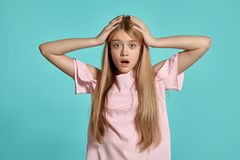 Studioporträt eines blonden Jugendlichen des schönen Mädchens in einem rosa T-Shirt, das über einem blauen Hintergrund aufwirft lizenzfreie stockfotos