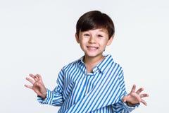 Studioporträt eines Jungen, der entlang der Kamera und des Angebens anstarrt lizenzfreie stockfotos