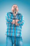 Studioporträt eines jungen Impresarios mit dem Mikrofon Lizenzfreie Stockbilder
