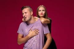 Studioporträt eines jungen Paares in der Freizeitkleidung, die gestritten wird und einen Schritt hin zu Versöhnung unternommen is stockbild