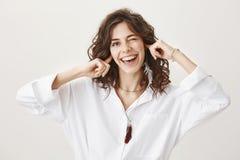 Studioporträt von spielerischen emotionalen netten Bedeckungsohren der erwachsenen Frau mit den Zeigefingern beim breit blinzeln  Stockfoto