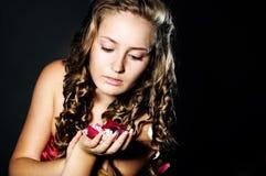 Studioportrait der jungen Frau mit den rosafarbenen Blumenblättern Lizenzfreie Stockfotografie