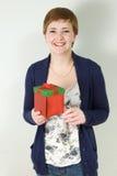 Studioportrait des Holding-Geschenkkastens der jungen Frau Stockfoto