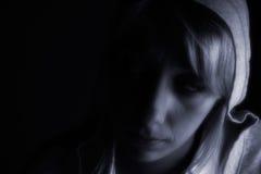 Studioportrait eines langen blonden Mädchens in der Dunkelheit Stockbild