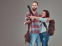 Studioportret die van mannelijke en vrouwelijke toeristen met rugzak en driepoot, in een studio knuffelen Stock Fotografie