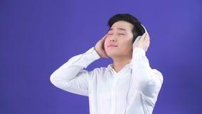 Studioportret van de knappe jonge mens van het Japanse behoren tot een bepaald ras en hoofdtelefoons stock footage