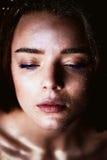 Studioportret van een mooi meisje met lang haar Schitter op uw gezicht Mooie ogen Donkere achtergrond geheimzinnig Stock Foto