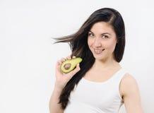 Studioportret van het mooie jonge vrouw stellen met een avocado over wit geïsoleerde achtergrond Royalty-vrije Stock Afbeelding