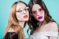 Studioportret van meisjes Twee mooie vrouwen met heldere make-up en de ronde glazen op blauwe achtergrond, sluiten omhoog horizon stock foto