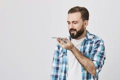Studioportret van volwassen gebaarde mannelijke modelholdingssmartphone dichtbij mond terwijl het spreken daarin met in verwarrin royalty-vrije stock foto's