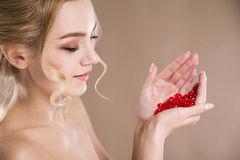 Studioporträt einer Blondine in ihren Handroten Kapseln des Vitamins Stockbild