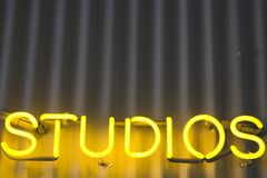 Studios Sign. A bright yellow, neon sign on a corrugated metal building says STUDIOS Stock Photography