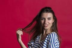 Studioschot van een mooie mooie die vrouw tegen een lege rode studiomuur wordt geïsoleerd royalty-vrije stock fotografie
