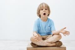 Studioschot van geïmponeerd nieuwsgierig blond kind met vitiligozitting met gekruiste voeten en het dalen kaak, het uitspreiden p stock foto's