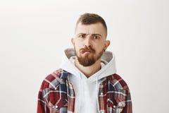 Studioschot van knappe doordrongen stedelijke mannelijke schaatser met modieus kapsel en baard die tong, het fronsen, het maken t stock fotografie