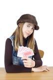 Studioskott av den blonda flickan med det bruna locket som spelar kort och ser in i kameran som isoleras på vit Arkivfoton