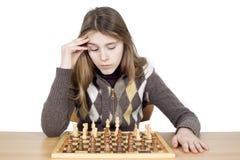 Studioskott av den eftertänksamma unga flickan som ner ser på schackbrädet och Intensely tänker om schackstrategi som isoleras på Royaltyfri Bild
