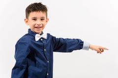 Studioskott av den gulliga lyckliga pojken som ler och pekar fingret på sid Arkivfoton