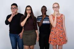 Studioskott av den olika gruppen av mång- etniska vänner med fingret Arkivfoto