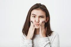 Studioskott av den unga attraktiva europeiska kvinnliga modellen som pressar henne kinder med förbryllat och tvivelaktigt uttryck arkivbild