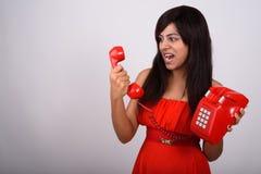 Studioskott av den unga persiska kvinnan som ser ilsken, medan ropa fotografering för bildbyråer