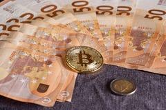 Studioskott av det fysiska guld- myntet för bitcoin på 50 euroräkningsedlar Bitcoin är en crypto valuta för blockchain Arkivfoto