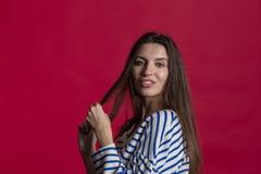 Studioskott av en älskvärd härlig kvinna mot en tom röd studiovägg arkivfoto