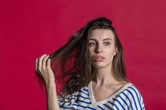 Studioskott av en älskvärd härlig kvinna som isoleras mot en tom röd studiovägg arkivfoto