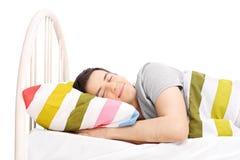 Studioskott av en bekymmerslös man som sover i säng Royaltyfria Foton