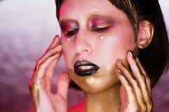 Studioskott av en guld- Glittery kroppkvinna fotografering för bildbyråer