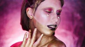 Studioskott av en guld- Glittery kroppkvinna Purpurfärgad bakgrund stock video