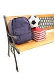 Studioskott av en träbänk med böcker, skolapåsen och footbal Royaltyfria Foton