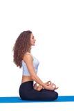 Studioskott av en ung passformkvinna som gör yoga arkivbild