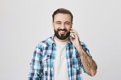 Studioskott av europén för vuxen man med moderiktig frisyr och skägget som gärna ler, medan tala på telefonen och se royaltyfri bild