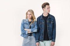 Studioskott av missnöjda par som bär tillfällig kläder som tillbaka står till tillbaka att rynka pannan deras framsidor Disharmon arkivfoto