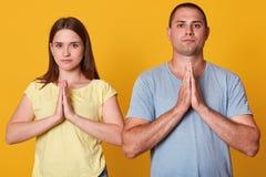 Studioskott av tacksamma tacksamma unga par som rymmer händer, i att be gest, ärlig förälskelse, mannen och kvinnan direkt på kam arkivbilder