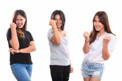 Studioskott av tre lyckliga unga asiatiska kvinnavänner som ler whi arkivfoto