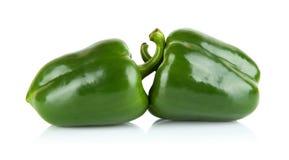 Studioskott av två gröna spanska peppar som isoleras på vit Arkivfoton