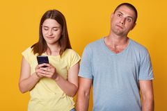 Studioskott av unga par, attraktivt kvinnligt smsande meddelande på smartphonen som är manlig med fundersamt ansiktsuttryck som s arkivbild