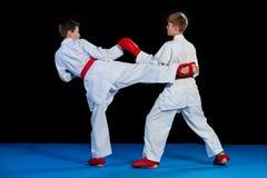 Studioskottet av gruppen av ungar som utbildar karatekampsporter royaltyfria foton