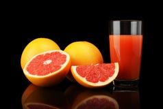 Studioskottet skivade tre grapefrukter med fruktsaft isolerad svart Arkivfoton