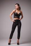Studiospruit van aantrekkelijke vrouw in sexy zwarte bovenkant en broeken Royalty-vrije Stock Foto