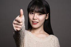Studiostående av asiatiska kvinnor för lycklig tjugotal med tummar upp Royaltyfria Bilder