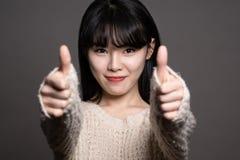 Studiostående av asiatiska kvinnor för lycklig tjugotal med tummar upp Royaltyfri Foto