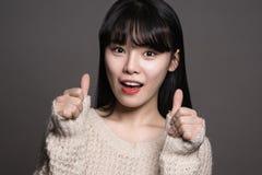 Studiostående av asiatiska kvinnor för lycklig tjugotal med tummar upp Royaltyfri Fotografi