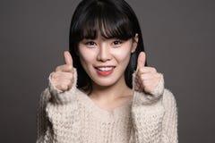 Studiostående av asiatiska kvinnor för lycklig tjugotal med tummar upp Arkivfoton
