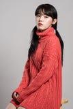 Studiostående av asiatiska kvinnor för tjugotal som stirrar på kamerasammanträde i stol Arkivbild