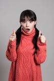 Studiostående av den asiatiska kvinnan för tjugotal med hållande tummar för förvånad blick upp Royaltyfri Fotografi