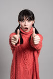 Studiostående av den asiatiska kvinnan för tjugotal med hållande tummar för förvånad blick upp Arkivbilder